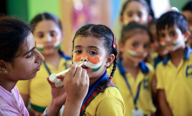School children with their faces painted with Indian flag colors take part in a programme in an Independence Day function at a school in Jammu on Saturday. (PTI Photo)