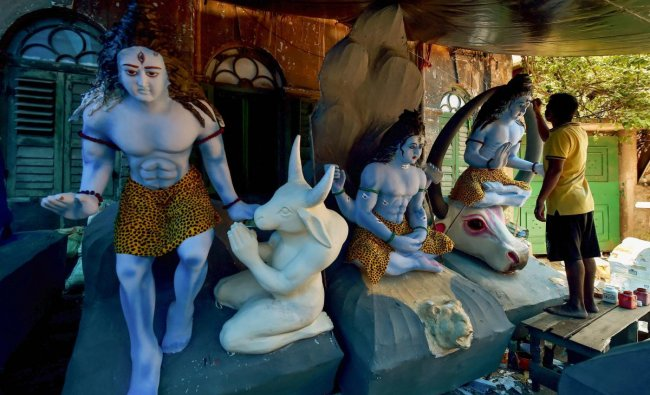 An artist gives finishing touches to the idols of Lord Shiva at his workshop during the holy month of Shravan in Kolkata on Friday, August 10, 2018. (PTI Photo)