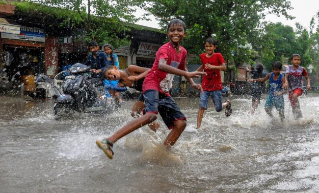 Children play on a waterlogged street during rainfall, in Amritsar. (PTI Photo)