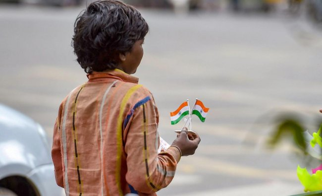 A child selling the tricolour waits for customers at a roadside during the 72nd Independence day celebration at Manesk Shaw parade ground in Bengaluru on Wednesday, Aug 15, 2018. (PTI Photo)