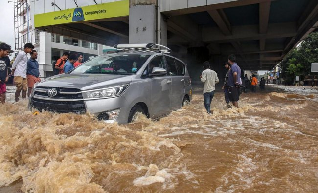People wade across a waterlogged street at a flood-affected region following heavy monsoon rainfall, in Kochi on Thursday, Aug 16, 2018. (PTI Photo)