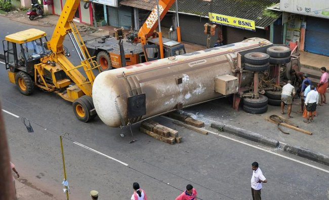 A crane is used to remove the a gas-tanker that overturned at Pallikkunnu in Kannur on Saturday, Aug 25, 2018. PTI