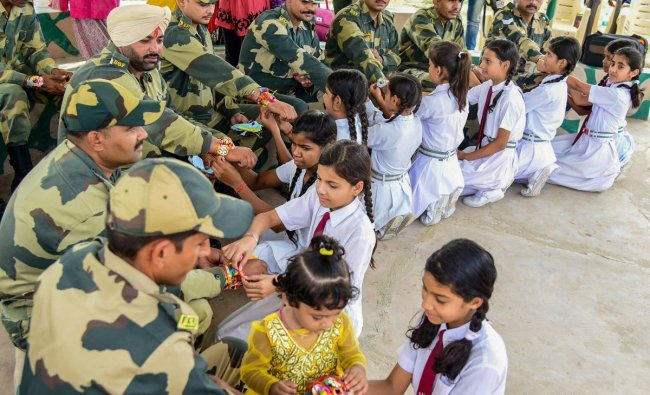 Students tie rakhis on the wrists of BSF personnel on the eve of Raksha Bandhan, in Bikaner on Saturday, Aug 25, 2018. PTI