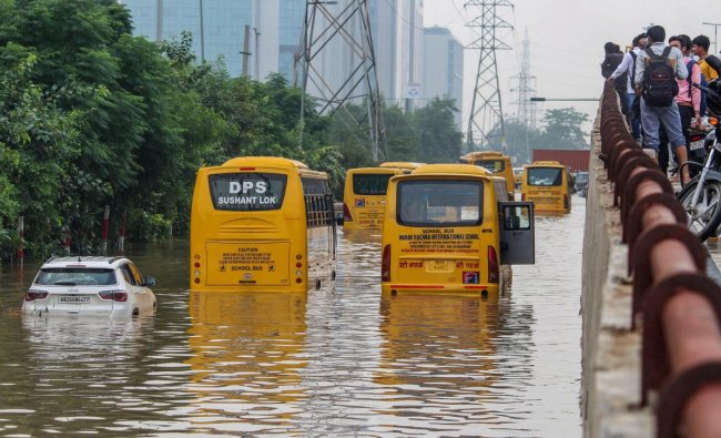 School buses moves slowly at a waterlogged road after heavy rains in Gurugram on Tuesday, Aug 28, 2018.