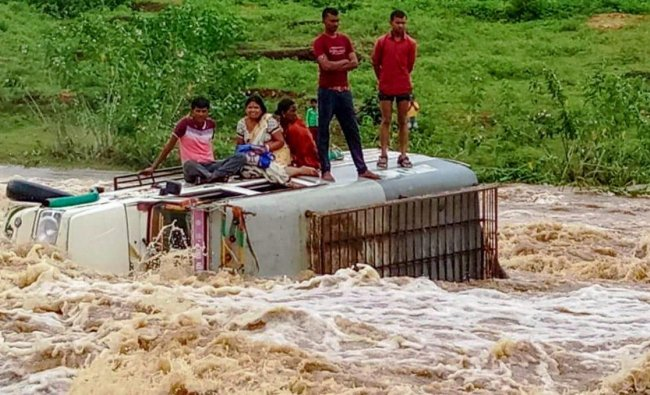 People stand atop vehicle that collapsed into flooded water following heavy monsoon rains, in Latehar on Monday, Sept 3, 2018. (PTI Photo)