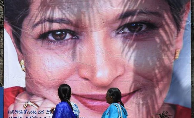 Two women walk past a poster of slain journalist Gauri Lankesh during the \'Freedom of Expression Meet\', organised on the occasion of first death anniversary of Gauri, in Bengaluru, Wednesday, Sept 5, 2018. (PTI Photo/Shailendra Bhojak)
