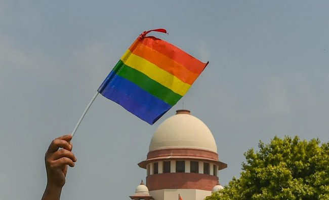 An activist waves a rainbow flag (LGBT pride flag) after the Supreme Court verdict which decriminalises consensual gay sex, outside the Supreme Court in New Delhi. (PTI Photo)