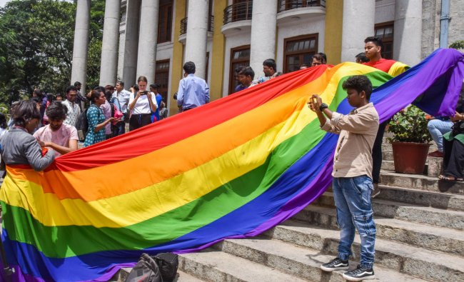 LGBTQ community people, with a rainbow flag, celebrate the Supreme Court verdict which decriminalises consensual gay sex, in front of Town Hall in Bengaluru. (DH Photo)