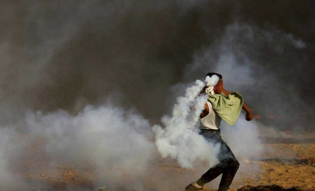 A protesters throws back a teargas canister fired by Israeli troops while other burn tires near the fence of Gaza Strip border with Israel, during a protest, east of Gaza City, Friday, Sept. 7, 2018. A teenager was killed and dozens of other Palestinians injured by Israeli fire at a border protest, Gaza officials said. AP/PTI