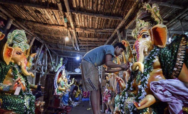 An artist gives finishing touches on an idol of Lord Ganesh at a studio on the eve of Ganesh Chuturthi festival in Kolkata, Wednesday, Sept 12, 2018. PTI Photo