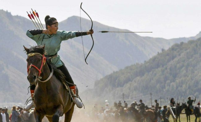 In this photo taken on Thursday, Sept. 6, 2018, a women releases an arrow during an archery competition during the Third Nomad Games, in Cholpon-Ata, 250 kilometers (156 miles) of Bishkek, Kyrgyzstan. The Central Asian nation of Kyrgyzstan held its biennial Nomad Games to promote and celebrate traditional sports of nomadic people. The week-long competition, which is held in a gorge near the picturesque Lake Issyk-Kul, feature traditional sports of nomad peoples such as horseback wrestling and goat polo. AP