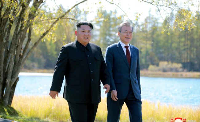 This picture taken on September 20, 2018 and released by Korean Central News Agency (KCNA) via KNS shows North Korea\'s leader Kim Jong Un (L) and South Korean President Moon Jae-in (R) walking together during a visit to Samjiyon guesthouse near Mount Paektu in Samjiyon. - Kim Jong Un and Moon Jae-in visited the spiritual birthplace of the Korean nation on September 20, for a show of unity after their North-South summit gave new momentum to Pyongyang\'s negotiations with Washington. (Photo by KCNA VIA KNS / v