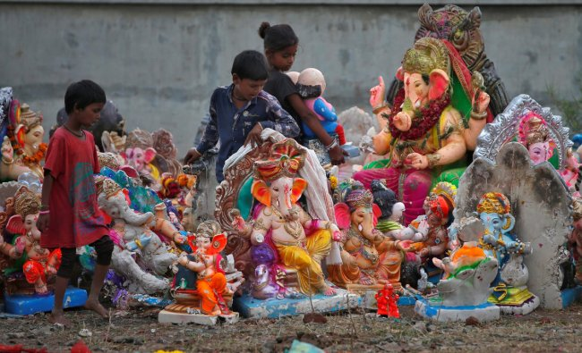 Children assemble idols of Hindu god Ganesh, the deity of prosperity, after collecting them from a pond a day after their immersion, in Ahmedabad, India, September 24, 2018. REUTERS/Amit Dave