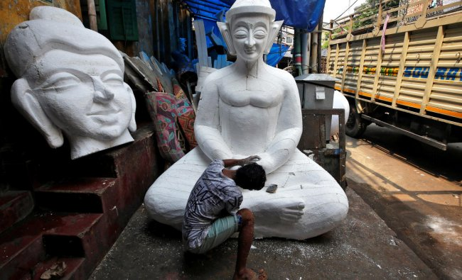 A man works on a Buddha idol made of polystyrene, which will be used to decorate a pandal, or a temporary platform, ahead of the Durga Puja festival in Kolkata, India September 25, 2018. REUTERS/Rupak De Chowdhuri