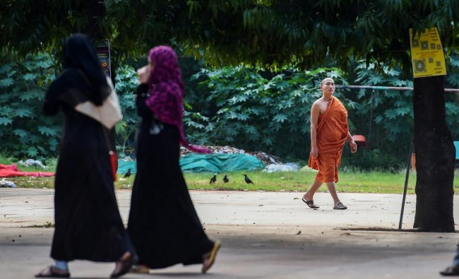 Bengaluru: A Buddhist monk walks past activists during the \'Baatein Aman Ki\' campaign that aims to sensitise people about violence against women, in Bengaluru, Thursday, Sept 27, 2018. (PTI Photo/Shailendra Bhojak)