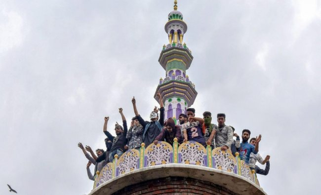Budgam: People raise slogans from the tomb of a mosque, where militants were hiding during an encounter with security forces, at Panzan Chadoora area of Budgam district near Srinagar, Thursday, Sept 27, 2018. Five persons, including three militants, were killed in three separate incidents. (PTI Photo)