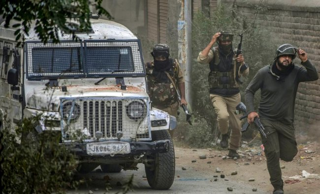 Budgam: Special Operation Group (SOG) of Jammu and Kashmir Police run towards the mosque where militants were hiding during an encounter, at Panzan Chadoora area of Budgam district near Srinagar, Thursday, Sept 27, 2018. Five persons, including three militants, were killed in three separate incidents. (PTI Photo)