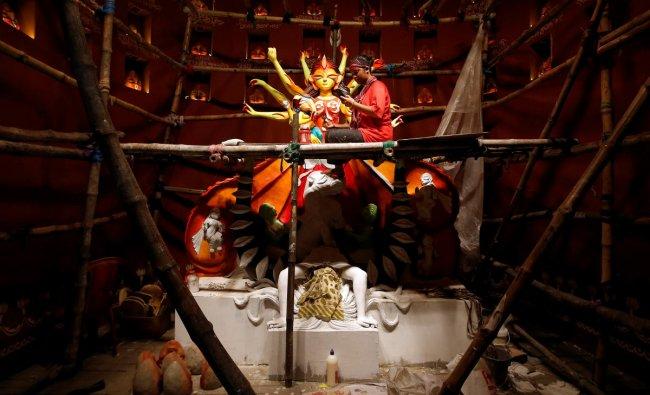 Artist Upashona Chatterjee checks her mobile phone as she decorates an idol of the Hindu goddess Durga at a pandal, or a temporary platform, for the upcoming Hindu festival of Durga Puja in Kolkata. (Reuters Photo)