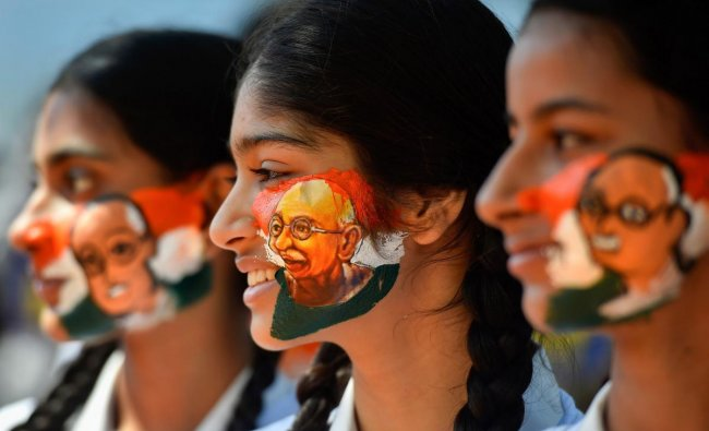 Students paint their face with Mahatma Gandhi image ahead of his birth anniversary, in Chennai, Monday Oct 01,2018. (PTI Photo)