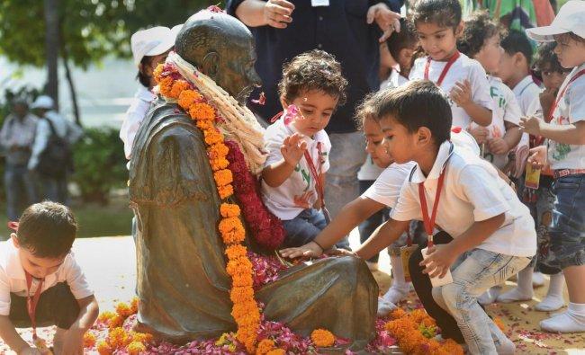 School students pay tribute to Mahatma Gandhi on his 149th birth anniversary, at Sabarmati Ashram in Ahmedabad. (PTI Photo)