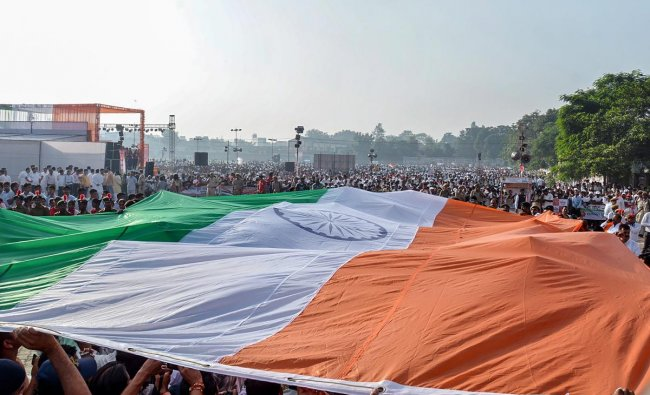 People carry an Indian tricolour to be placed at a height of 131ft ahead of its hoisting by Union Textile Minister Smriti Irani, in Muzzafarnagar, Tuesday, Oct 2, 2018. (PTI Photo)