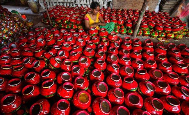 An artisan decorates earthern pitchers used during Gujarati folk dance \'Garba\', ahead of Navratri festival, in Ahmedabad. (PTI Photo)