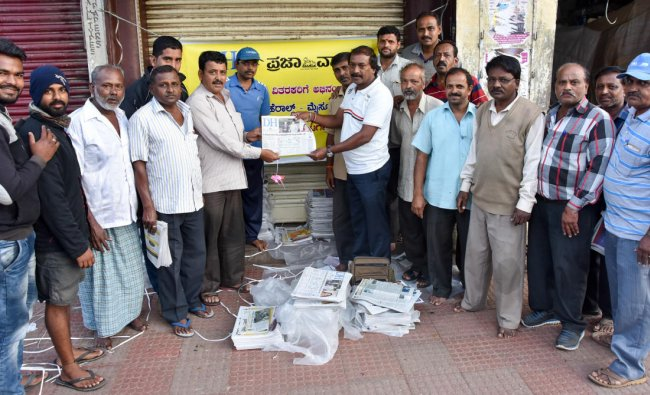 Newspaper agents release all pages colour edition of Deccan Herald and Prajavani, near Devaraja Market in Mysuru on Friday. DH photo