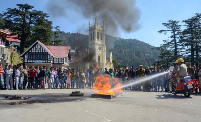 Firefighters extinguish fire during a demonstration on the occasion of International Day for Natural Disaster Reduction, at Ridge in Shimla. PTI