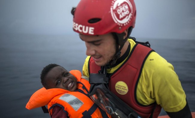 A member of Spanish NGO Pro activa Open Arms holds a baby rescued at a dinghy at Alboran Sea, about 40 miles (64 kms) from the Spanish coasts. The Open Arms is now based at Motril port in order to start operating in the western Mediterranean area. AP/PTI