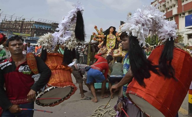Traditional drummers perform as an idol of goddess of Durga is carried to a puja pandal, at Sealdah Station in Kolkata. PTI