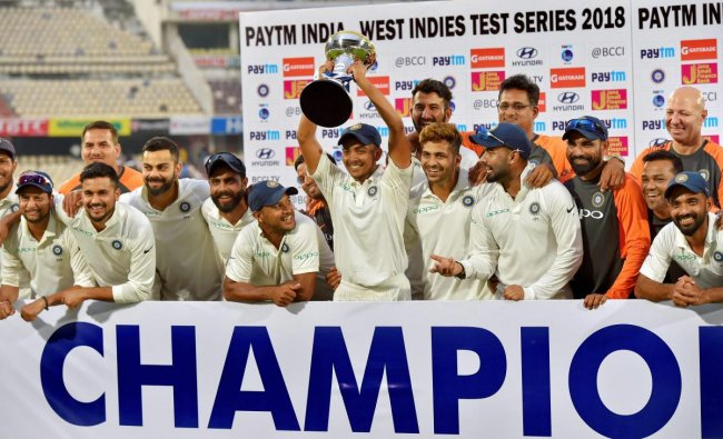 Indian cricket team players poses with winning trophy after beating West Indies in the second cricket test match, in Hyderabad. PTI