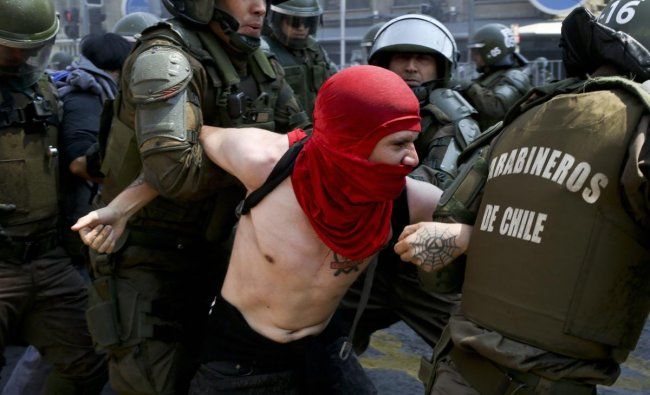 A protester is detained by police during a march against the commemoration of the discovery of the Americas, organized by indigenous groups demanding autonomy and the recovery of ancestral land, in Santiago, Chile. Protesters also demonstrated against Chile\'s anti-terrorism law, under which many Mapuche Indians are under arrest. AP/PTI