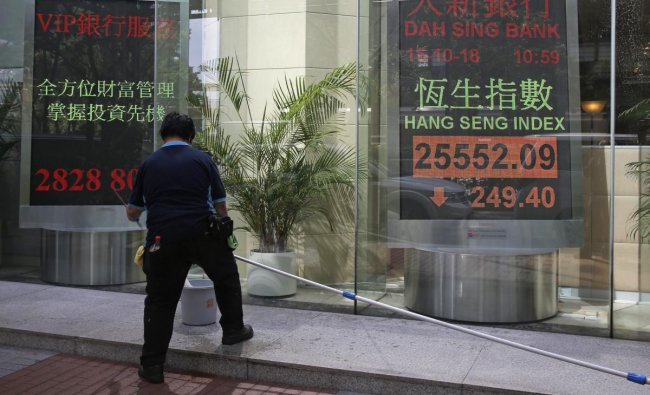 A worker stands in front of an electronic board showing Hong Kong share index outside a bank In Hong Kong. Asian stocks slipped Monday, as investor worries continued about global trade tensions and prospects for economic growth. AP/PTI