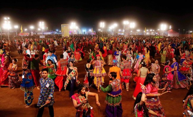Youngsters, dressed in traditional attire, participate in mass \'Garba\' and \'Dandiya\' programme during Navratri celebrations, in Jaipur. PTI