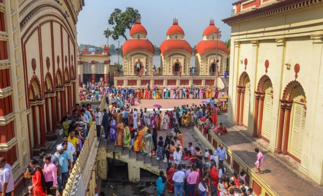 Devotees wait in a queue to offer prayers on the occasion of \'Maha Saptami puja\' during the ongoing Durga puja festival, at Dakshineswar Kali Temple in Kolkata. PTI