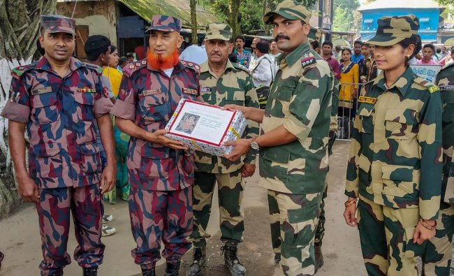Border Security Force (BSF) and Border Guard of Bangladesh (BGB) officials greet each other on the occasion of Durga Puja festival, at the International Check Post in South Dinajpur. PTI