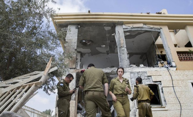 Israeli soldiers stand in front of a house that was hit by a missile fired from Gaza Strip, in the city of Beersheba, southern Israel. A medical service said a woman and her three children, whose home was struck, were being treated for shock after they fled to their shelter upon being awoken by warning sirens. AP/PTI