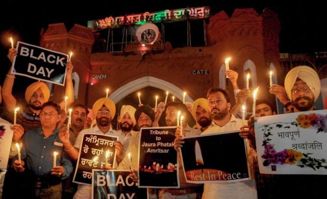 Members of National Human Rights and crime control organisation participate in a candlelight vigil to pay tribute to victims of Amritsar train accident, in Amritsar. PTI Photo