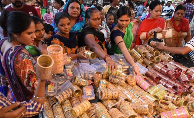 Women browse through bangles on display at a stall on the eve of the \