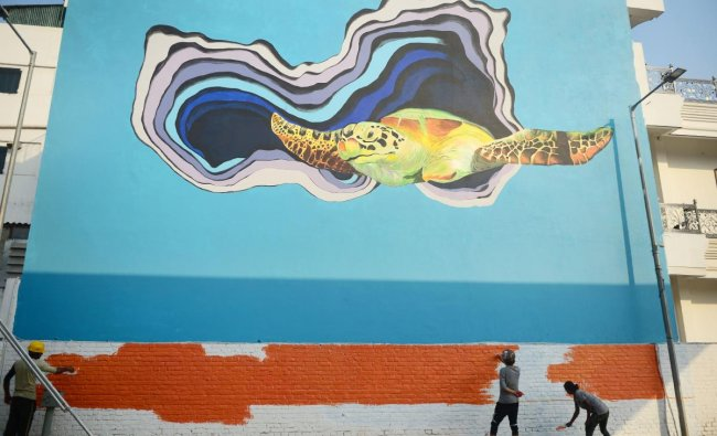 Indian artists paint a wall of a building as part of an ongoing project \'Paint my City\' in Allahabad on October 27, 2018. (Photo by SANJAY KANOJIA / AFP)