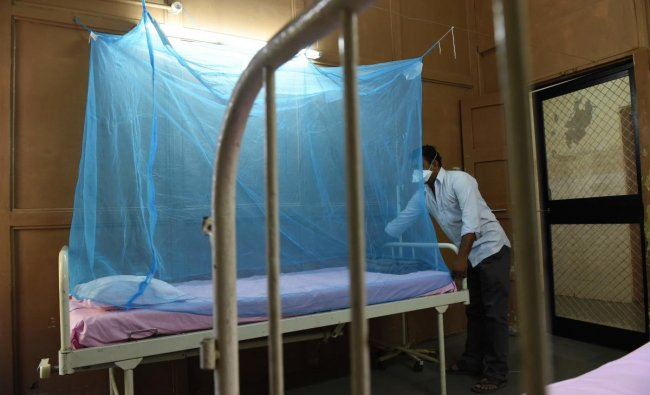 An attendant places a mosquito net to a bed at an isolation ward for Zika Virus patients at Ahmedabad Municipal Corporation run Vadilal Sarabhai (VS) Hospital in Ahmedabad on October 27, 2018. - Gujarat Health Department started taking precautions against Zika virus by major cleanliness drive and preparing Isolation Wards in Ahmedabad hospitals for possible Zika affected patients. (Photo by SAM PANTHAKY / AFP)