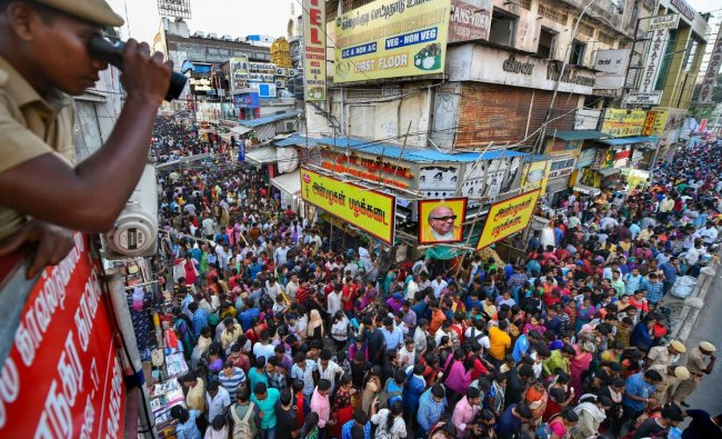 A security personnel keeps watch on the crowd packed area of Ranganathan Street during Diwali shopping, in Chennai, Sunday, Oct 28, 2018. (PTI Photo)