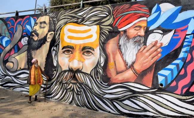 A sadhu walks past a mural painting created as a part of the ongoing project \'Paint my City\' for the upcoming Kumbh Mela festival, in Allahabad, Tuesday, Oct 30, 2018. (PTI Photo)