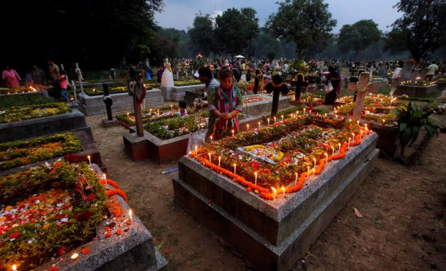 People pray after lighting candles on the grave of their relatives at a cemetery during the observance of All Souls Day, in Kolkata, India, November 2, 2018. REUTERS