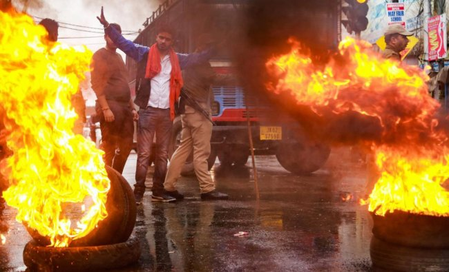 Youth burn tyres during a protest against the killing of BJP state secretary Anil Parihar (52) and his brother Ajeet (55), by militants while they were returning to their Kishtwar home yesterday, in Jammu, Friday, Nov 02, 2018. (PTI Photo)