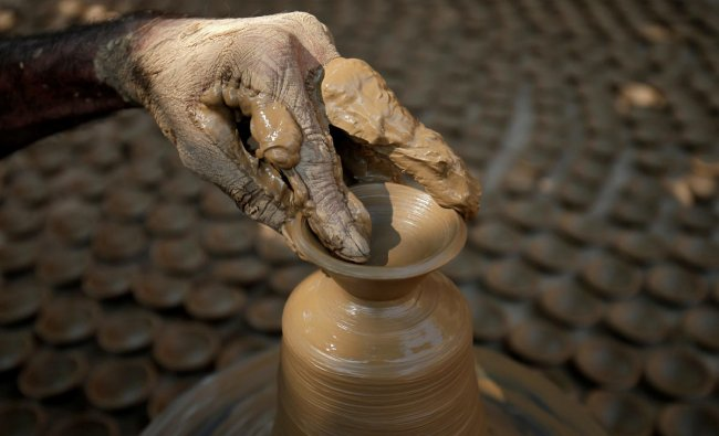 A man makes earthen lamps which are used to decorate temples and homes during the Hindu festival of Diwali, at a workshop in Ahmedabad, India November 2, 2018. REUTERS
