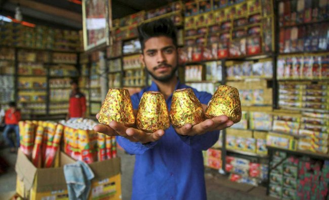A shopkeeper arranges firecrackers at his shop ahead of the festival of Diwali, in Jammu, Sunday, Nov 4, 2018. (PTI Photo)