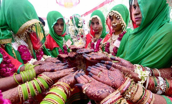 Brides pose for a photograph with their henna applied hands during a mass marriage ceremony in Ahmedabad on Sunday. November 4, 2018. (PTI Photo/Santosh Hirlekar)
