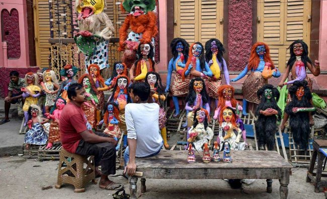 Vendors sit beside the mythological characters of demons made from clay, on the eve of \'Kali Puja\', at an artisan village in Kolkata, Monday, November 05, 2018. PTI Photo