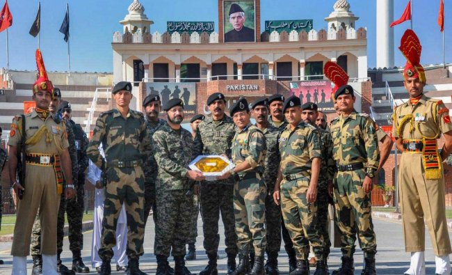 Pakistani border wing commander Usman Khalid (L) exchanges a gift of sweets with his Indian counterparts Border Security Force Commandant Sudeep on the occasion of the Diwali festival at the India-Pakistan Wagah border near Amritsar on Wednesday, November 7, 2018. PTI Photo